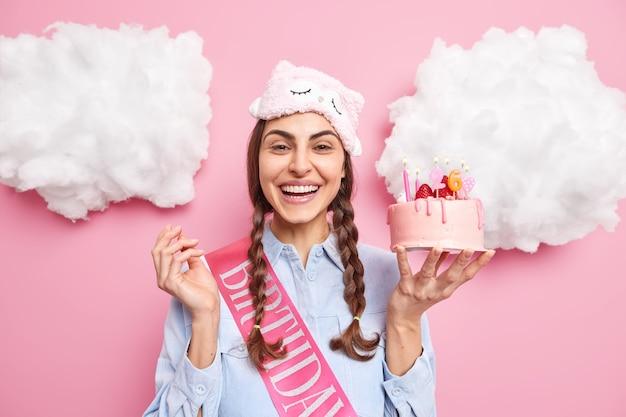 Женщина счастливо улыбается, держит вкусный клубничный торт со свечами, празднует день рождения, наслаждается домашней вечеринкой, носит повязку на лбу, повседневную рубашку, изолированную на розовой стене