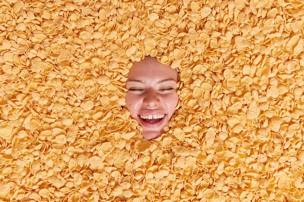 Woman smiles happily keeps eyes closed being in good mood buried in cornflakes feels very happy has healthy breakfast eats low calorie food keeps to diet
