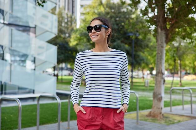 여자는 선글라스를 끼고 행복하게 웃고 있다 줄무늬 점퍼와 빨간 반바지는 도시 공원을 가로질러 걷다 여름 산책로를 즐긴다 도시 환경 근처에서 신선한 공기를 마시며 서 있다