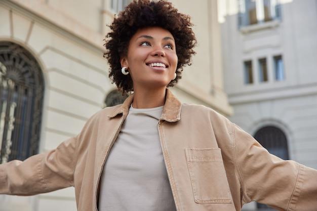 La donna sorride positivamente si sente libera vestita con una giacca beige ha un'espressione felice passeggiate nella città antica gode di un'escursione