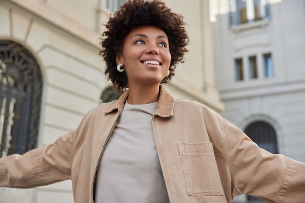 여자는 긍정적으로 베이지색 재킷을 입고 자유를 느끼고 고대 도시에서 산책을 즐긴다 행복한 표정을 하고 있다