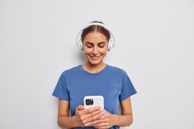 여자는 재생 목록에 휴대 전화 다운로드 노래를 긍정적으로 보유하고 헤드폰에서 오디오 트랙을 듣고 흰색에 파란색 티셔츠를 입는다