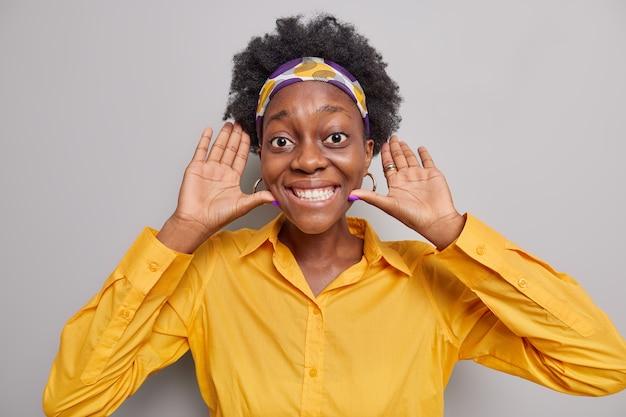 女性の笑顔は歯を見せて手のひらを顔の近くに保ち、誰かが灰色で隔離された黄色のシャツのヘッドバンドを着て楽しませます