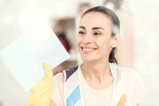 The woman smiles and wipes the window at home