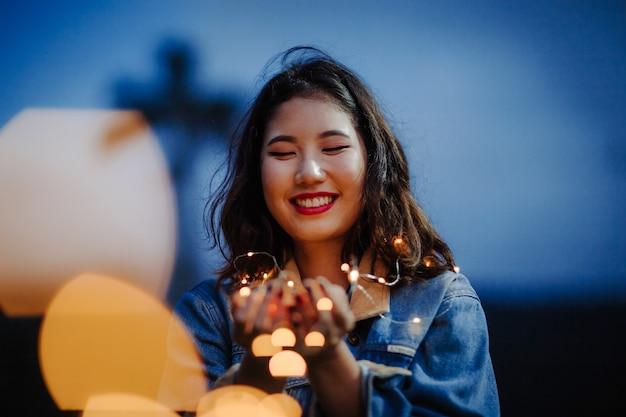 笑顔で夜にストリングライトを保持している女性