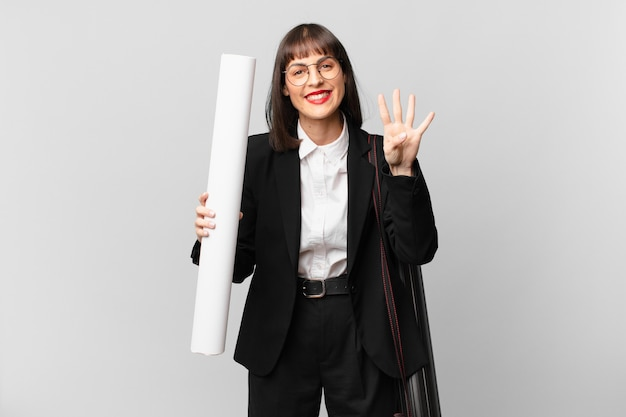 Женщина улыбается и выглядит дружелюбно, показывает номер четыре или четвертый с рукой вперед, отсчитывая