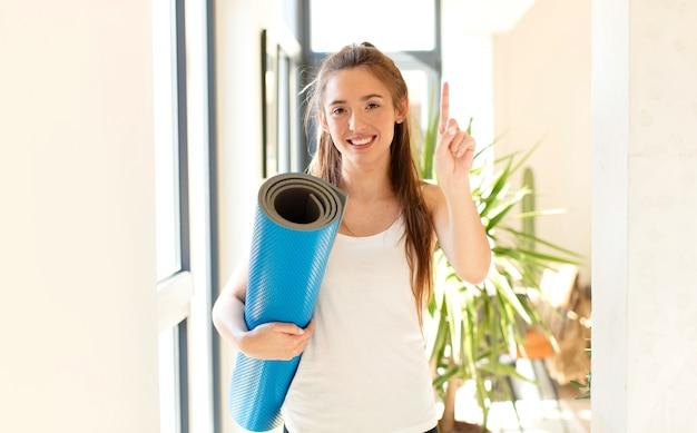 미소하고 친절하게 보이는 여성, 앞으로 손으로 번호 하나 또는 첫 번째 표시, 카운트 다운