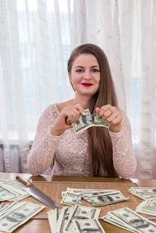 笑顔で百ドル紙幣をリッピングする女性