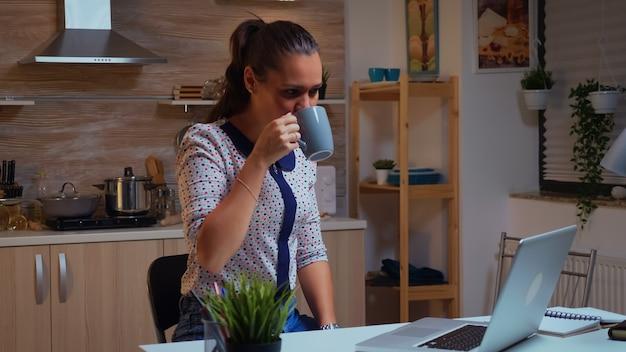 집에서 일하는 동안 화상 회의 중에 웃고 인사하는 여자. 작업 읽기 쓰기, 검색을 위해 초과 근무를 하는 현대 기술 네트워크 무선을 사용하는 바쁜 집중 직원