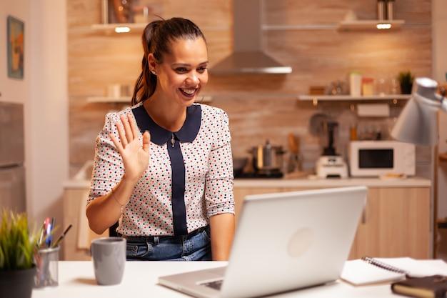 在宅勤務中のビデオ会議中に笑顔で挨拶する女性。深夜に最新のテクノロジーを使用して、仕事、ビジネス、キャリア、ネットワーク、ライフスタイル、ワイヤレスで残業している従業員。