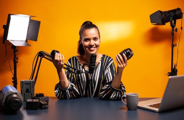 フォロワーのためにレンズレビューを記録しながらカメラに微笑んでいる女性