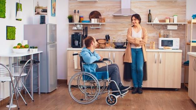 彼と話している間車椅子で障害のある夫に微笑んでいる女性。麻痺障害者障害者愛と人間関係からの移動の助けを得ることが困難な