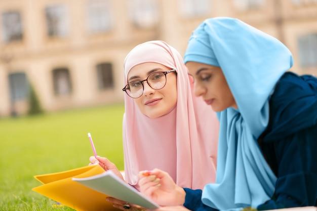 웃는 여자. 친구와 함께 공부하는 동안 웃 고 파란색 hijab에서 아름 다운 젊은 여자