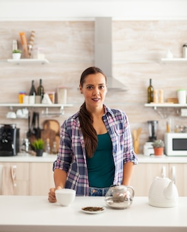 Woman smiling at camera in kitchen holding cup of hot tea during breakfast