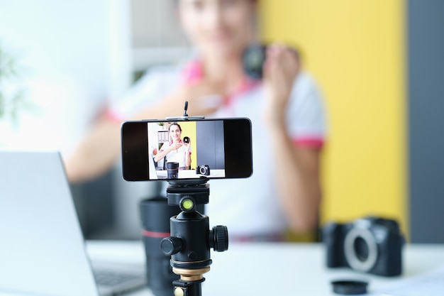 Woman smiling at camera while recording lens review for followers influencer on social media