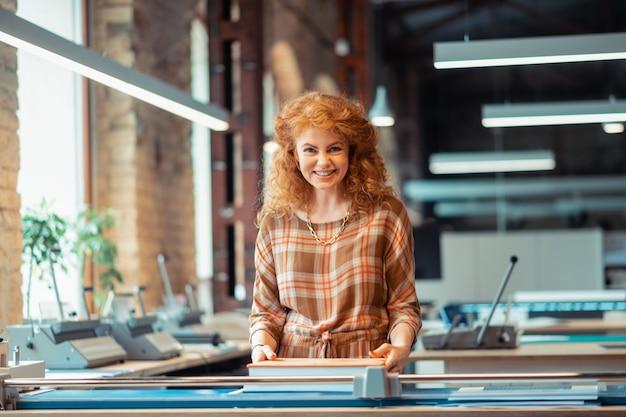Женщина улыбается. веселая рыжая женщина в красивом платье работает в издательском офисе улыбается