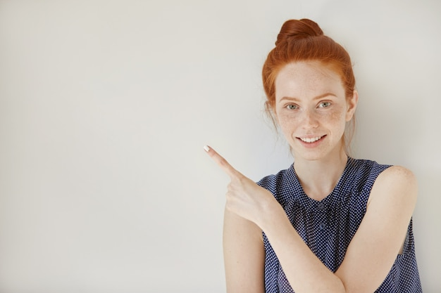 Woman smiling cheerfully and pointing her index finger upwards