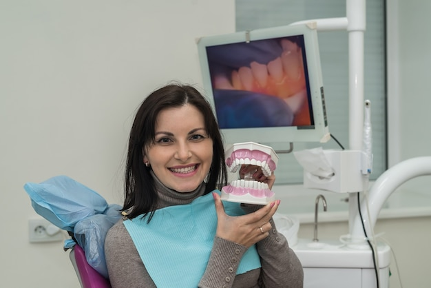 Woman smiling in dentistry with jaw model