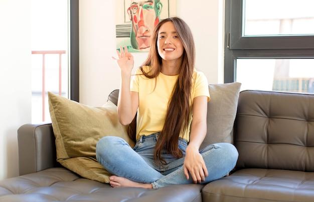 Женщина счастливо и весело улыбается, машет рукой и приветствует вас или прощается