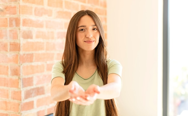 Женщина счастливо улыбается с дружелюбным, уверенным, позитивным взглядом, предлагая и показывая объект или концепцию