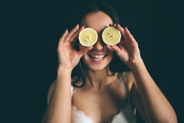 Женщина улыбается счастья крышка глаз игривый лимонный портрет. в белом нижнем белье.