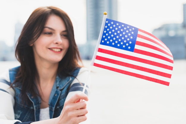 Woman smiling and holding american flag in hand