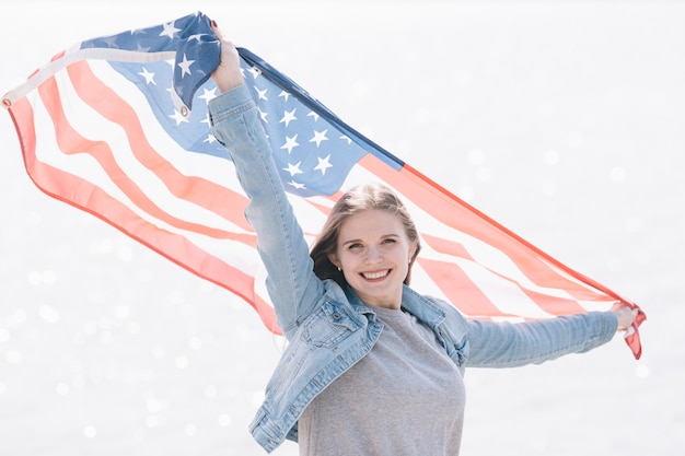 Woman smiling and holding american flag high in sky