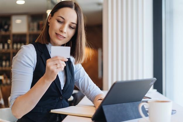 태블릿 컴퓨터 구매 및 결제, 직불 카드 구매 또는 금융, 라이프 스타일 및 전자 상거래 개념의 거래를 사용하는 소녀와 함께 온라인 쇼핑 신용 카드를 들고 웃는 여자.