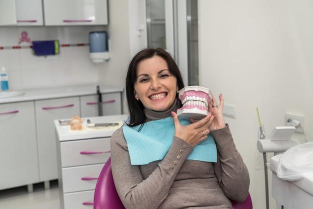Женщина улыбается в стоматологии с моделью челюсти