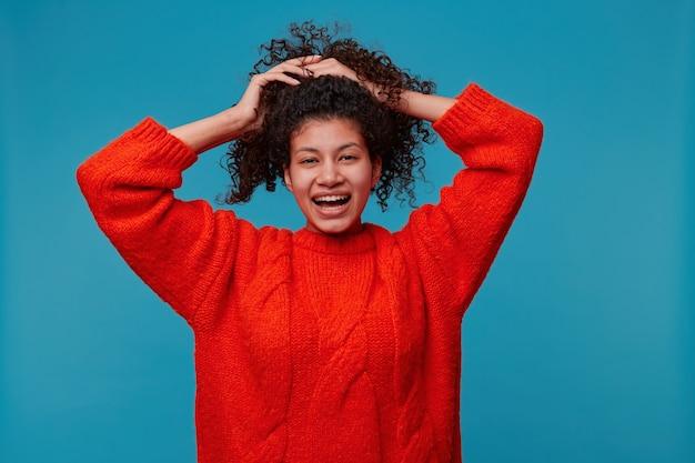 幸せなかわいい顔と赤いセーターを着て楽しんで笑って笑っている女性