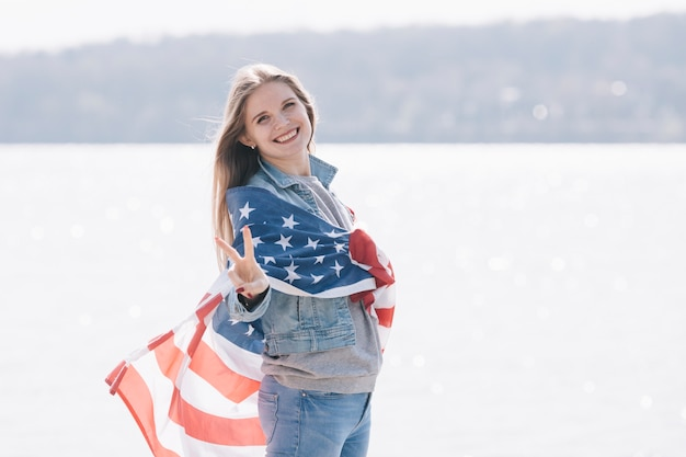 Woman smiling and looking at camera wrapped in american flag