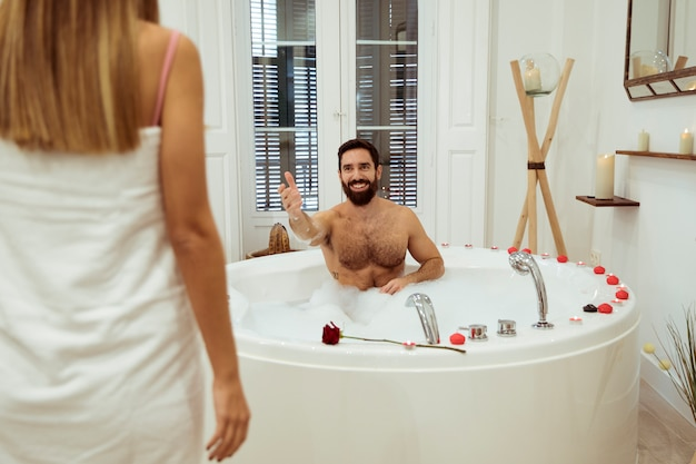 Woman and smiling man in spa tub with foam