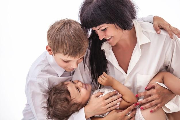 子供の男の子と女の子にキスする母親の笑顔の女性。スタジオ、孤立した、幸せな、白。