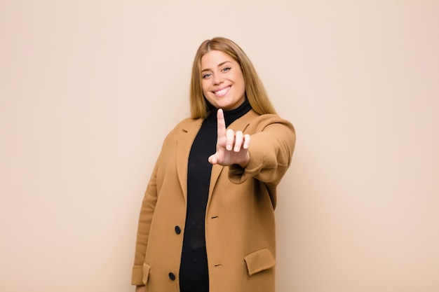 Woman smiling proudly and confidently making number one pose triumphantly, feeling like a leader