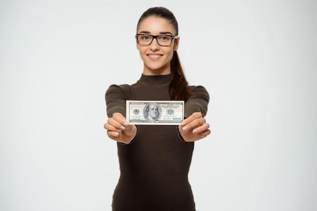 笑みを浮かべて、ドルを示す女性