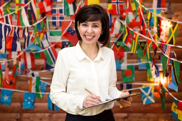 Woman smiling successfully negotiating internationally. wall of flags of the world