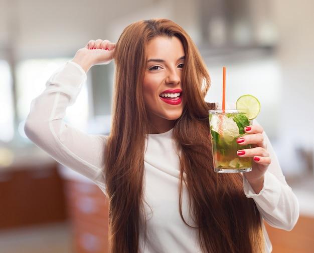 ドリンク付きガラスを保持しながら笑顔の女性
