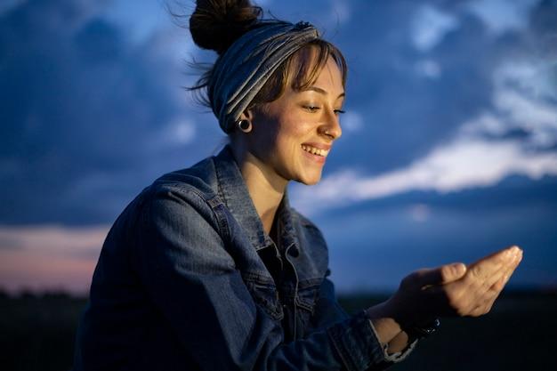 그녀의 손에 뭔가 흥미로운 것을 들고 웃는 여자