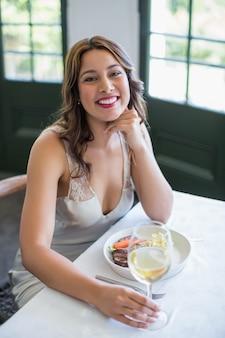 Женщина улыбается, держа бокал в ресторане
