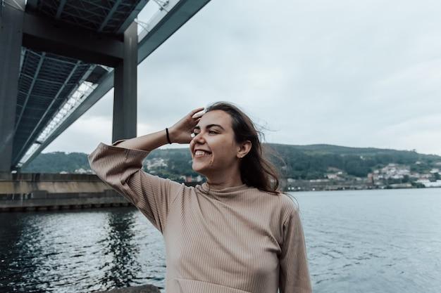 Женщина улыбается, глядя в камеру с копией пространства под мостом, концепции отдыха на море
