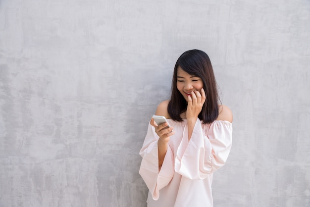 Woman smiling while looking at her cellphone