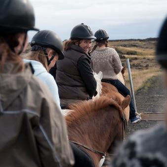アイスランドの馬を横に乗っている間に笑っている女性
