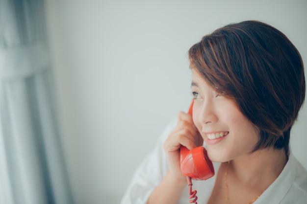 赤い電話で話しながら笑顔女性がクローズアップ