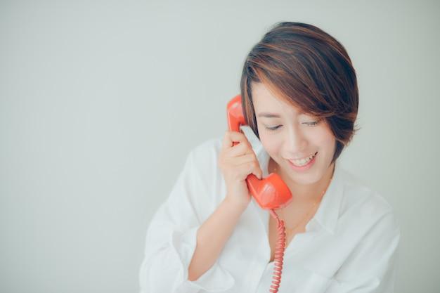 赤い電話で話しながら笑顔の女性