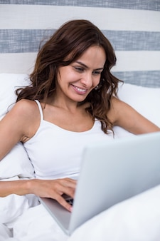 Woman smiling while using laptop on bed