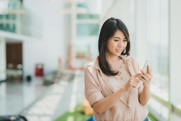 Woman smiling while using smartphone in modern office