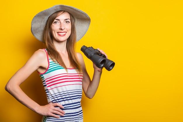 Женщина улыбается в шляпе и полосатом платье, держа бинокль на желтом пространстве.