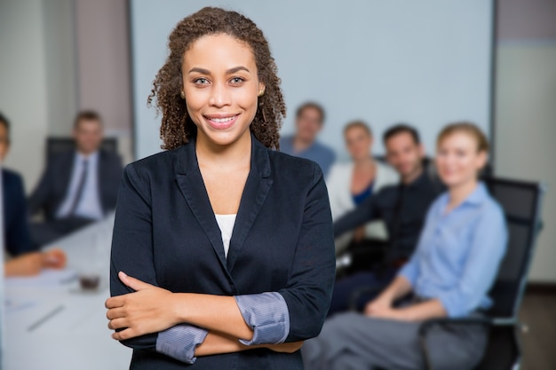 Woman smiling with arms crossed and colleagues out of focus