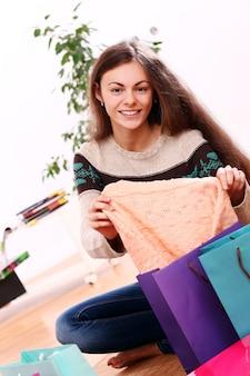 Женщина улыбается с красочными сумок