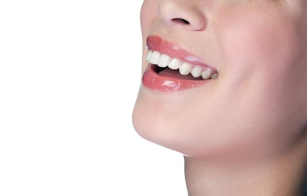Женщина улыбается с большими зубами на белом фоне